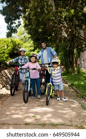 Portrait of parents and children standing with bicycle in park on a sunny day