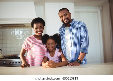 Portrait of parents and daughter in kitchen at home