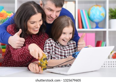 Portrait of parents and daughter playing computer game with laptop