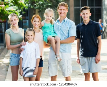 Portrait of parents with four children in different ages taking promenade in city