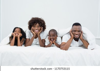 Portrait of parents and kids African-American lying on bed at home