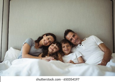 Portrait of parents and kids sitting on the bed