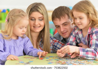 Portrait of parents playing with adorable little daughters