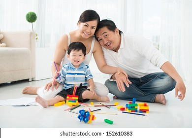 Portrait of parents playing with his son in lego constructions at home