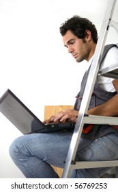 Portrait of a parquet layer sitting on a ladder in front of a laptop computer