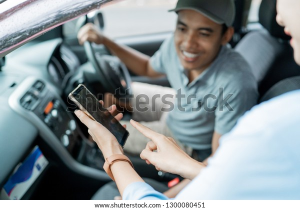portrait of passenger showing his smartphone application to the driver how much to cost to pay