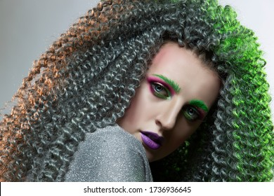 Portrait of Passionate Caucasian Girl With Frizzy Colorful Hair and Artistic Decorative Makeup.Posing Against Black. Horizontal Image Orientation