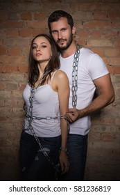 Portrait of passionate couple posing with chains near brick wall