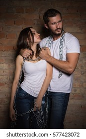 Portrait of passionate couple wearing white t-shirts posing with chains