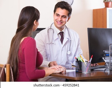 Portrait of patient and smiling therapeutist at desk in modern clinic