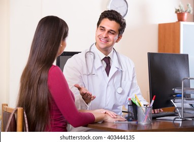 Portrait of patient and therapeutist at desk in modern clinic