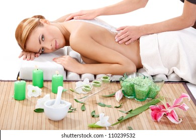 portrait of peaceful beautiful young woman getting back massage with sea salt at spa