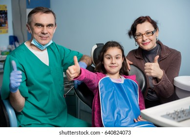 Portrait of pediatric dentist and young girl with her mother on the first dental visit at the dental office. People is smiling and showing thumbs up. Dentistry, medicine and health care concept