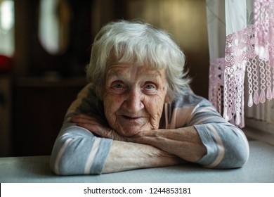 Portrait of a pensioner russian woman sitting at the table in home.
