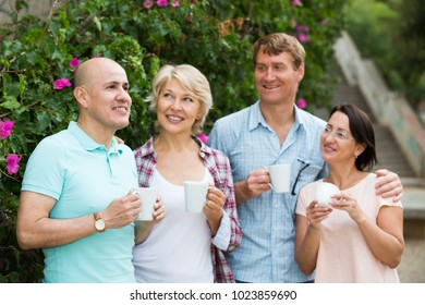 Portrait of pensioners talking in the park and drinking coffee