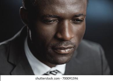 portrait of pensive african american businessman in suit looking away