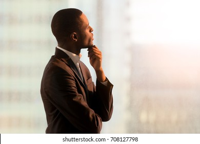 Portrait of pensive african american businessman standing near window and thinking about decision, dreaming of success, pondering new startup. Handsome black business leader imagining company future