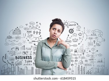 Portrait of a pensive African American woman standing near a gray wall with a business idea sketch drawn on it.