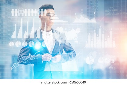 Portrait of a pensive Asian businessman buttoning his suit standing against a blurred cityscape with graphs in the foreground. Toned image double exposure mock up