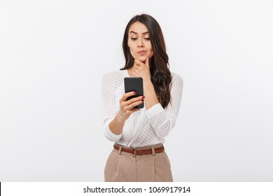 Portrait of a pensive asian businesswoman using mobile phone isolated over white background