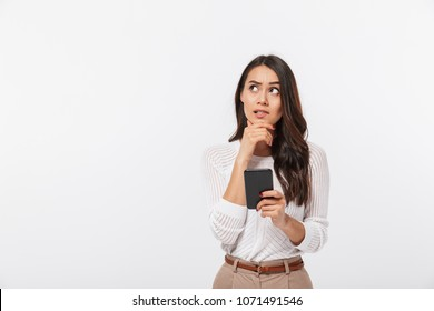 Portrait of a pensive asian businesswoman using mobile phone and looking away isolated over white background