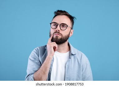 Portrait of pensive bearded man in glasses touching his chin, deep in thought over blue studio background. Puzzled young guy making choice or decision, dreaming about something