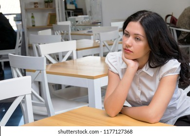 Portrait of pensive brunette model sitting in cafe with nice interior and looking away. Brooding girl waiting for order. Copy space in left side. People rest and lifestyle concept