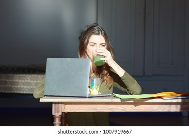 Portrait of pensive brunette woman drinking and eating healthy lunch sitting at table with scattered files and laptop.