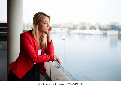 Portrait of pensive businesswoman looking out of an office balcony with beautiful seaport view on background, unhappy successful woman standing in exterior,blonde woman looking out of her window sadly