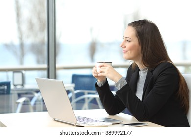 Portrait of a pensive businesswoman wearing suit thinking and planning looking outdoors through the window in a bar with the horizon in the background