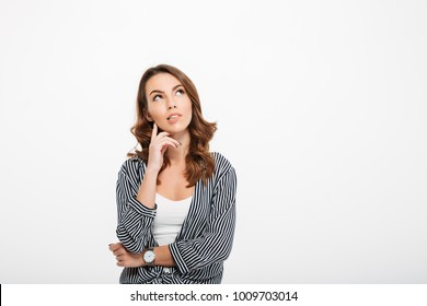 Portrait of a pensive casual girl looking away at copy space isolated over white background