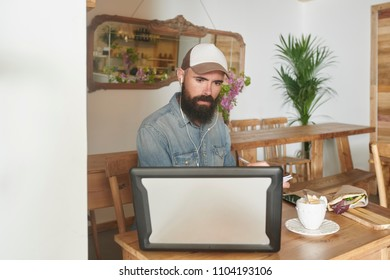 Portrait of pensive concentrated bearded worker in cap and shirt working on laptop and taking note in notebook sitting at table in modern cafe. He is having coffee and sandwich for lunch.