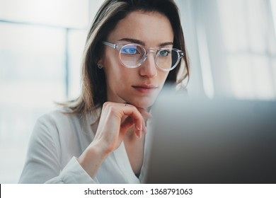 Portrait of pensive confident businesswoman working with laptop computer at modern office.Blurred background
