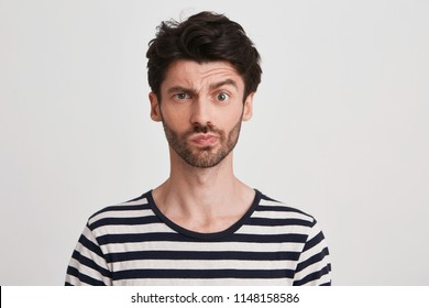 Portrait of pensive confused young man with bristle wears striped t shirt feels embarrassed and thinking isolated over white background Looks directly in camera