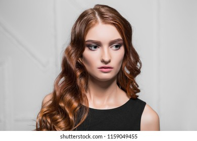Portrait of pensive curly woman posing in the studio