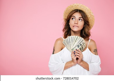 Portrait of a pensive doubtful girl in summer hat holding bunch of money banknotes and looking away at copy space isolated over pink background