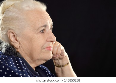 portrait of a��� pensive elderly woman on a black background