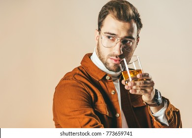 portrait of pensive fashionable man with glass of whiskey looking away isolated on beige