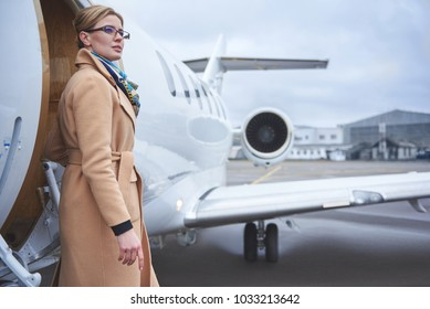 Portrait of pensive female standing near private airplane. Wealth and career concept