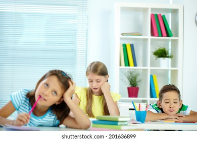 Portrait of pensive girl drawing at workplace with schoolmates near by
