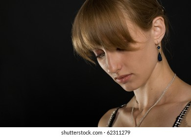 Portrait of a pensive girl on a dark background.  Natural hair color.