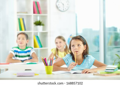 Portrait of pensive girl at workplace and her schoolmates on background looking attentively aside