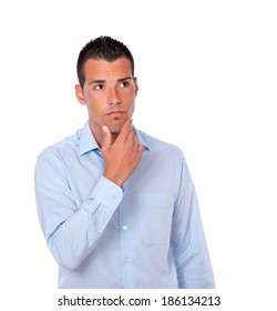 Portrait of a pensive hispanic man on blue stylish shirt looking at people on isolated background - copyspace