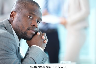 Portrait of pensive leader looking at camera in working environment