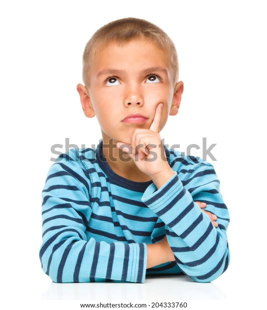 Portrait of a pensive little boy touching his cheek with index finger, isolated over white