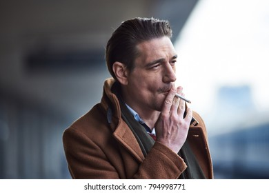 Portrait of pensive male smoking while situating outside. Smoke concept