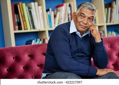 Portrait of pensive mature man sitting on the sofa