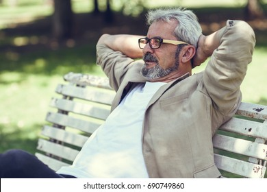 Portrait of a pensive mature man sitting on a bench in an urban park. Senior male with white hair and beard smiling wearing casual clothes. Old man wearing eyeglasses.