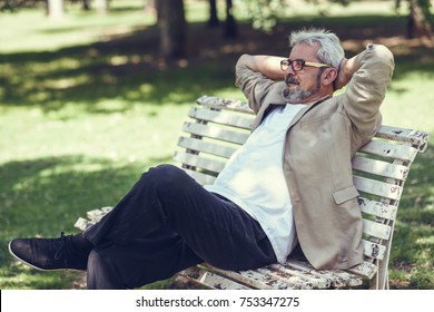 Portrait of a pensive mature man sitting on a bench in an urban park. Senior male with white hair and beard wearing casual clothes and eyesglasses.