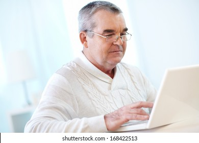 Portrait of pensive mature man working with laptop